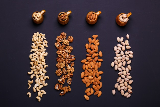 Assortment of nuts on a black slate - healthy snack. Premium Photo