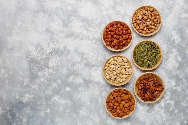 Assortment of nuts in ceramic plates. cashew, hazelnuts, walnuts, pistachio, pecans, pine nuts, peanut, raisins.top view Free Photo