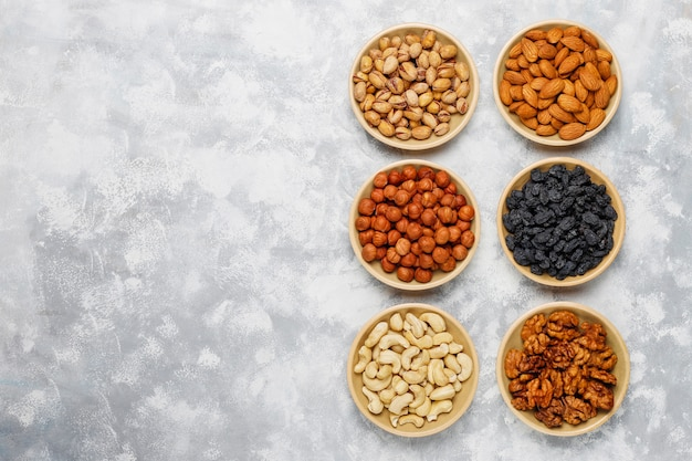 Assortment of nuts in ceramic plates. cashew, hazelnuts, walnuts, pistachio, pecans, pine nuts, peanut, raisins.top view Free Photo