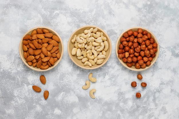 Assortimento di noci in piatti di ceramica. anacardi, nocciole, noci, pistacchi, noci pecan, pinoli, arachidi, uvetta.vista dall'alto Foto Gratuite