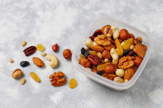 Assortment of nuts in plastic container. cashew, hazelnuts, walnuts, pistachio, pecans, pine nuts, peanut, raisins.top view Free Photo