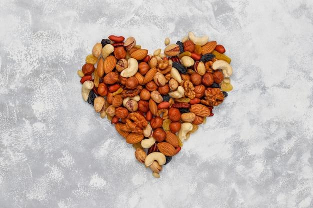Assortment of nuts shape of heart cashew, hazelnuts, walnuts, pistachio, pecans, pine nuts, peanut, raisins.top view Free Photo