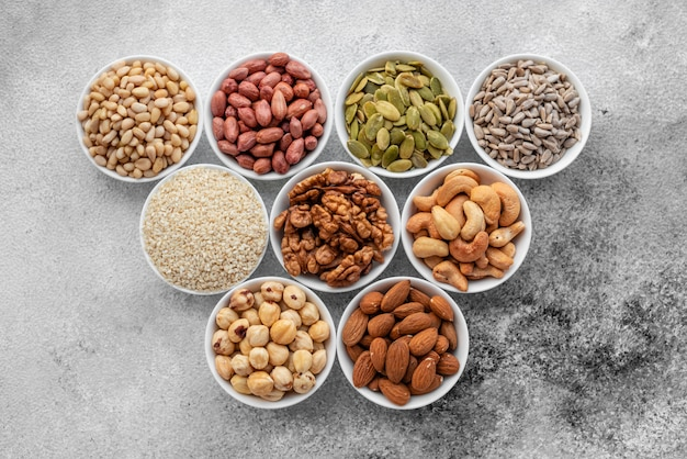 Assortment of nuts in white saucers on a concrete background. food mix background, top view, copy space, banner Premium Photo