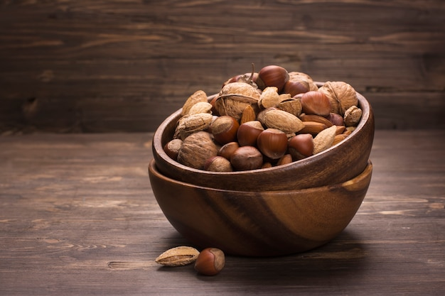 Assortment of nuts in wooden bowl ove rustic background Premium Photo