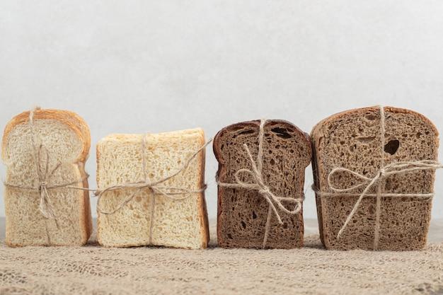 黄麻布にロープで結ばれたパンの品揃え。高品質の写真 無料写真