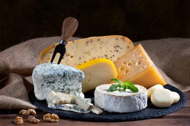 나무 배경에 다른 치즈 종류의 구색입니다. 치즈 배경. 프리미엄 사진