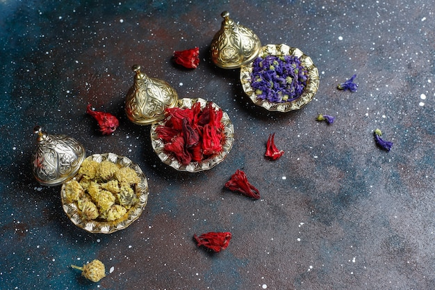 Ассортимент сухого чая в золотых винтажных мини тарелках. фон видов чая Бесплатные Фотографии