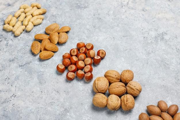 Ассортимент орехов на бетонной поверхности. фундук, грецкие орехи, орехи пекан, арахис, миндаль, вид сверху Бесплатные Фотографии