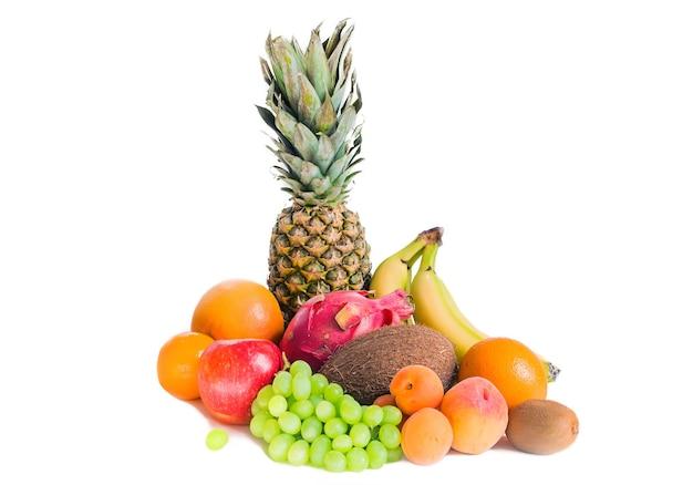 Ассорти из различных фруктов изолированные ананас, бананы, питайя, зеленый виноград, яблоко, кокос, персики, абрикосы, мандарины и киви. Premium Фотографии