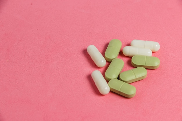 Assortment of pills, tablets and capsules on pink table. Premium Photo