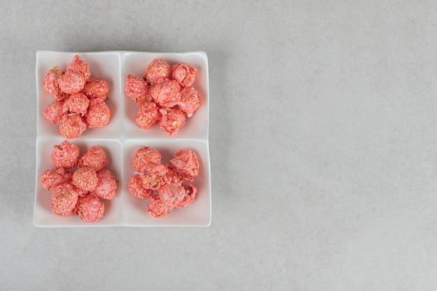 Piatto assortimento contenente quattro porzioni di popcorn ricoperto di caramelle su marmo. Foto Gratuite