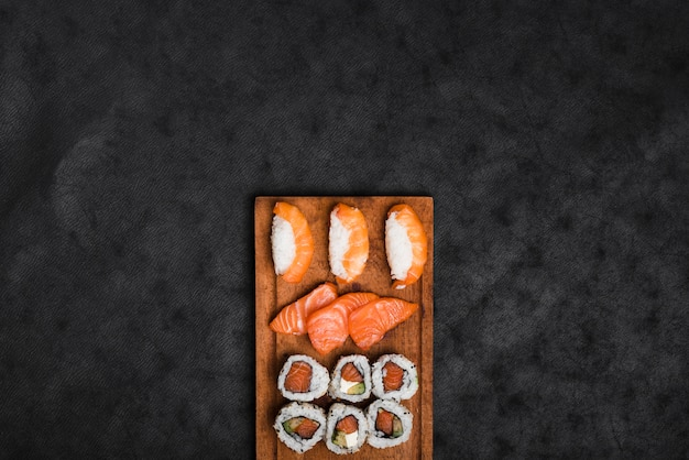 Assortment of sushi on wooden tray against black texture backdrop Free Photo