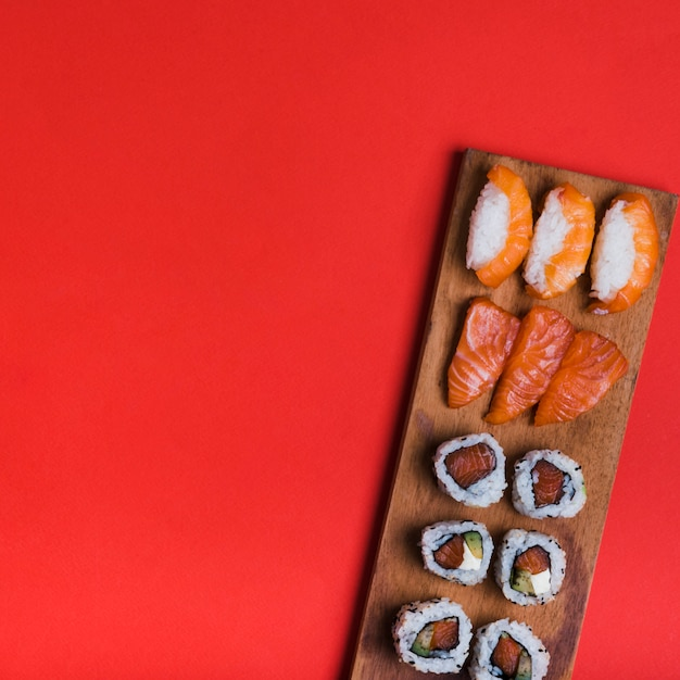 Assortment of sushi on wooden tray against red backdrop with copy space for writing the text Free Photo