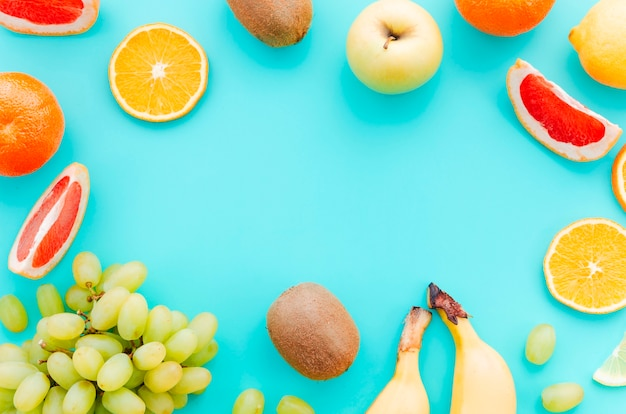 Assortment of tropical fruits on turquoise background Free Photo