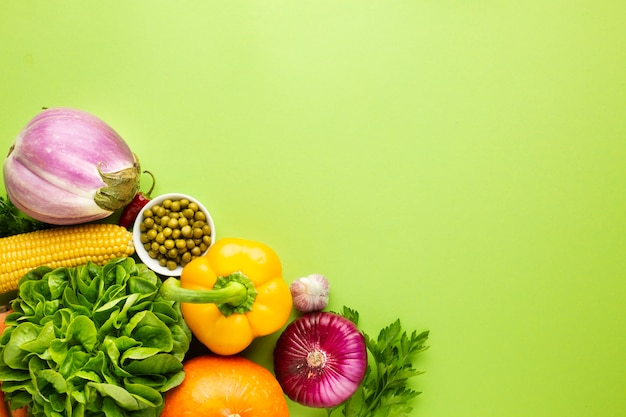Assortment of veggies on green background with copy space Free Photo