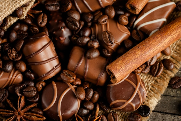 Assortment of white, dark, and milk chocolate. chocolate with cream, nuts, almonds, hazelnuts and cinnamon with coffee beans. sweet food and no diet concept. Premium Photo