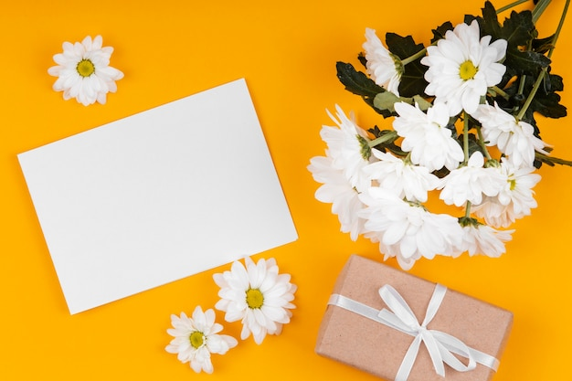 Assortment of white flowers with empty card and wrapped gift Free Photo