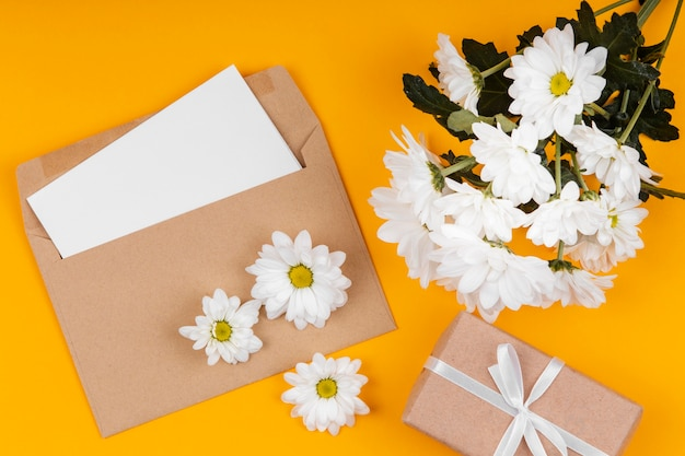 Assortment of white flowers with envelope and wrapped gift Free Photo