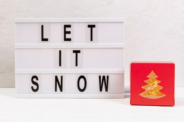 Assortment with let it snow sign and gift Free Photo