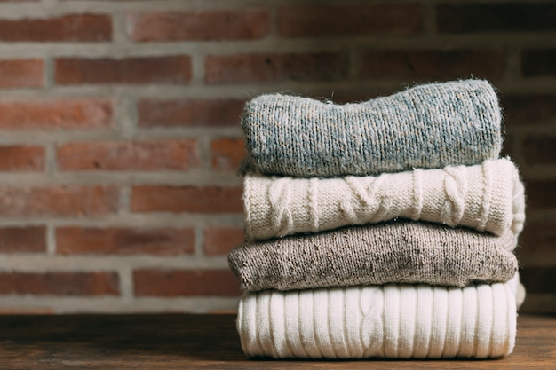 Assortment with warm clothes and brick wall Premium Photo
