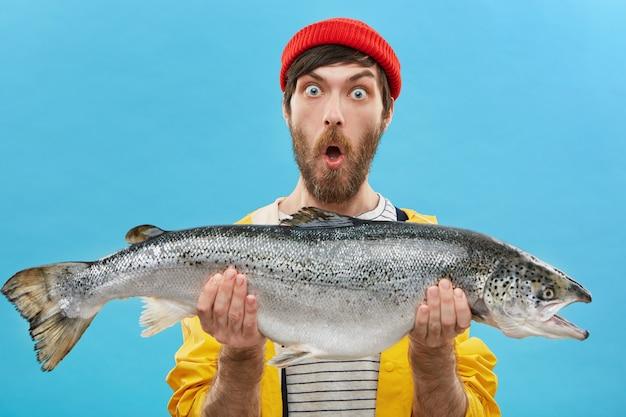 びっくりしたひげを生やしたひげを生やした漁師がカジュアルな服装をして、虫の目で見ている巨大な魚をつかみ、あごを落とし、そのような大きなマスやサーモンを捕まえました。 無料写真
