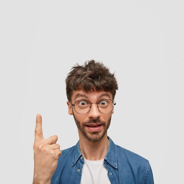 Удивленный бородатый молодой человек держит поднятым указательный палец Бесплатные Фотографии