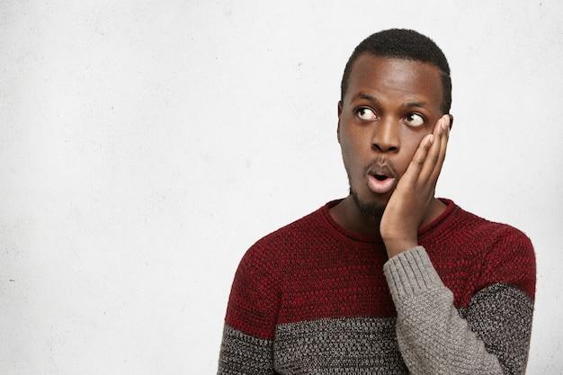 Удивленный черный человек трогательное лицо, глядя на copyspace на пустой серой стене, в шоке от чего-то. эмоциональный забавный молодой афроамериканский мужчина, выражающий шок, говоря: это невероятно! Бесплатные Фотографии