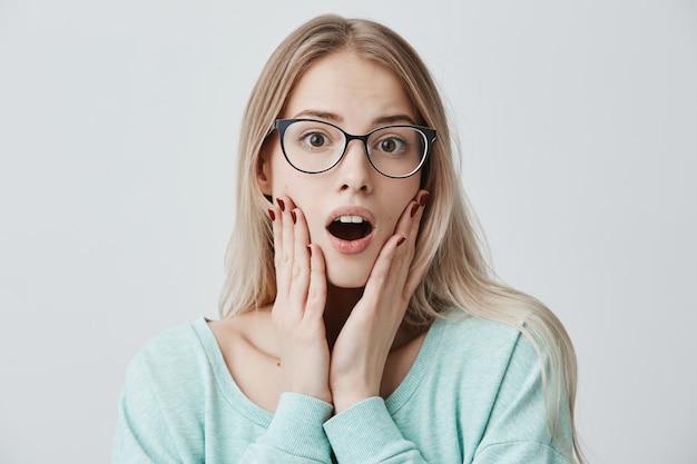 メガネのびっくりした金髪の女性モデルは、口を大きく開いて驚かせ、頬に手を当て続け、彼女がすぐにやらなければならない重要な義務を覚えています。衝撃と不信の概念 無料写真