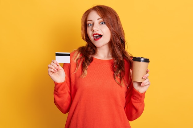 Astonished buyer finding offer online, holding take away coffee and credit card, has surprised facial expression, lady with red lips and wavy hair Free Photo