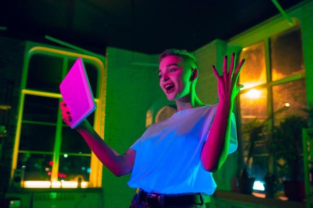 Stupito. ritratto cinematografico di donna alla moda in interni illuminati al neon. tonica come effetti cinematografici, colori luminosi al neon. modello caucasico utilizzando tablet in luci colorate al chiuso. cultura giovanile. Foto Gratuite
