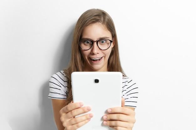 Удивленная эмоциональная забавная девочка-подросток в стильных очках, держащая обычный цифровой планшет и широко открывающая рот, потрясенная, читая новости или просматривая шокирующий контент в интернете Бесплатные Фотографии
