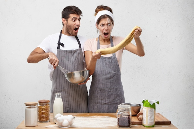 Astonished female chef stretches dough, looks with great surprisment, realizes drawbacks of preparation Free Photo