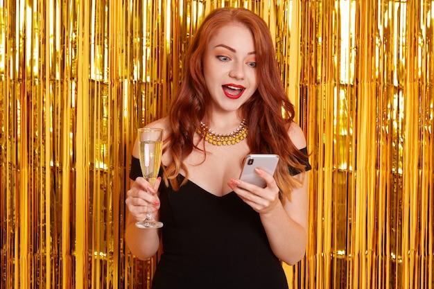 Donna stupita con labbra rosse e bocca spalancata, guardando con espressione facciale scioccata il suo dispositivo, ragazza che indossa un abito nero, in posa isolata su un muro decorato con orpelli dorati. Foto Gratuite