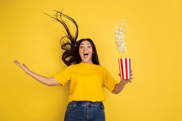 Popcorn stupito e volante. ritratto della donna caucasica isolato sulla parete gialla. bellissima modella bruna in casual. concetto di emozioni umane, espressione facciale, vendite, annuncio, copyspace. Foto Gratuite