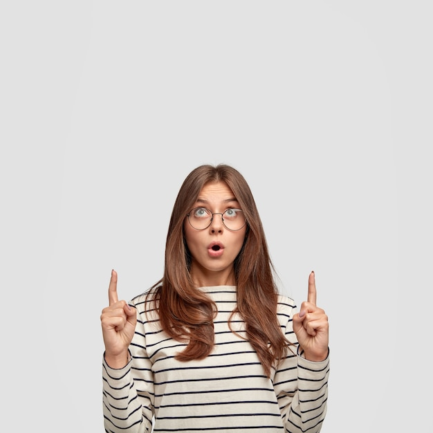 놀랍게도 갈색 머리를 가진 유럽 여성은 턱을 떨어 뜨리고 위층을 가리키며 광고 콘텐츠를위한 여유 공간을 보여주고 흰 벽에 서 있습니다. 광고 무료 사진