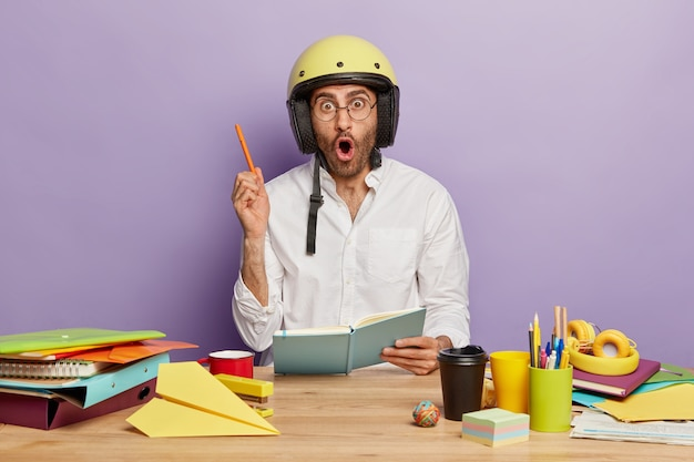 驚いた男の学生は、ノートにいくつかのアイデアを書き、ペンで腕を上げ、頭にヘルメットをかぶって、眼鏡をかけ、持ち帰り用のコーヒーを飲み、職場で必要な文房具に囲まれ、メモを取ります 無料写真