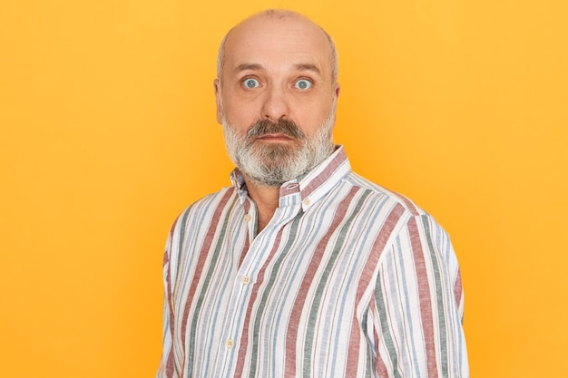 Astonished senior bald unshaven man wearing striped shirt opening eyes wide being caught by surprise, receiving sudden unexpected news posing isolated against yellow studio wall background Free Photo
