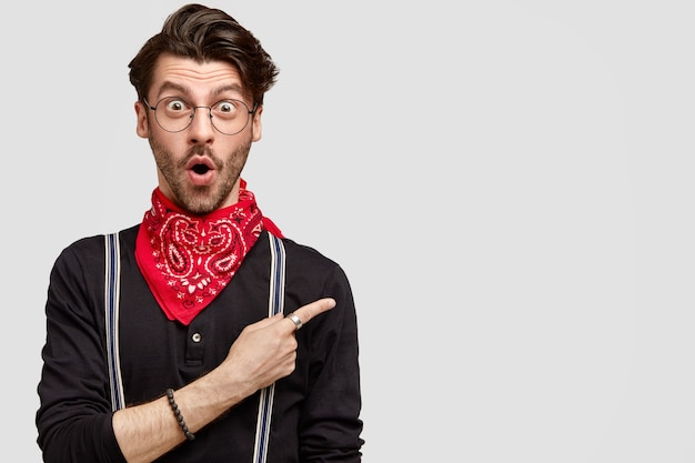Astonished stylish hipster has trendy haircut, opens mouth with surprisement, being not ready to advertise this item Free Photo