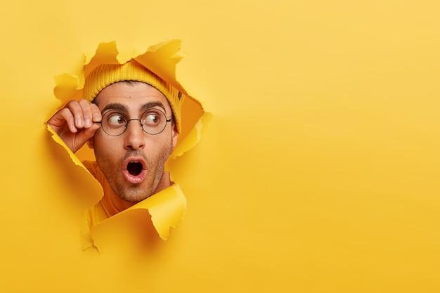 Un uomo sbalordito con la barba lunga guarda attraverso il foro nella carta gialla Foto Gratuite