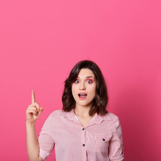 ピンクの背景に分離されたコピースペースに指を上向きにして、口を開けて立っている女性はカジュアルな服装を着て、驚いたように見えます。 無料写真