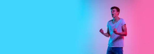 놀랐습니다. 네온 불빛에 그라데이션 블루 핑크 스튜디오 배경에 젊은 백인 남자의 초상화. 청소년, 인간의 감정, 표정, 판매, 광고의 개념. 캐주얼에 아름다운 모델. 전단 무료 사진