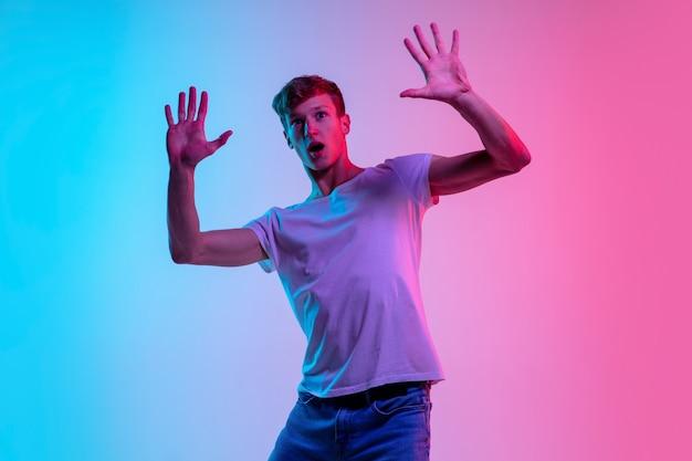 Удивлен. портрет молодого кавказского человека на градиентном сине-розовом фоне студии в неоновом свете. понятие молодости, человеческие эмоции, выражение лица, продажи, реклама. красивая модель в стиле casual. Бесплатные Фотографии