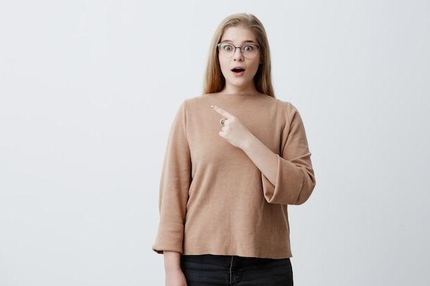 Astonished young female with blonde straight hair, wearing brown sweater, points at copy space with fore finger advertises something, keeps mouth widely opened. advertising and surprisment concept Free Photo