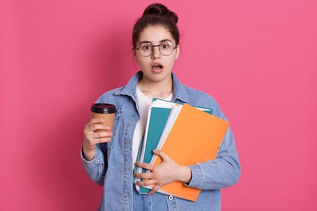 Удивленная молодая женщина с широко раскрытым ртом, держащая на вынос кофе и бумажную папку Бесплатные Фотографии