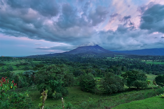 Astonishing panoramic view of the arenal volcano in costa rica after a forest partly covered with clouds during the sunset in a dramatic sky Premium Photo
