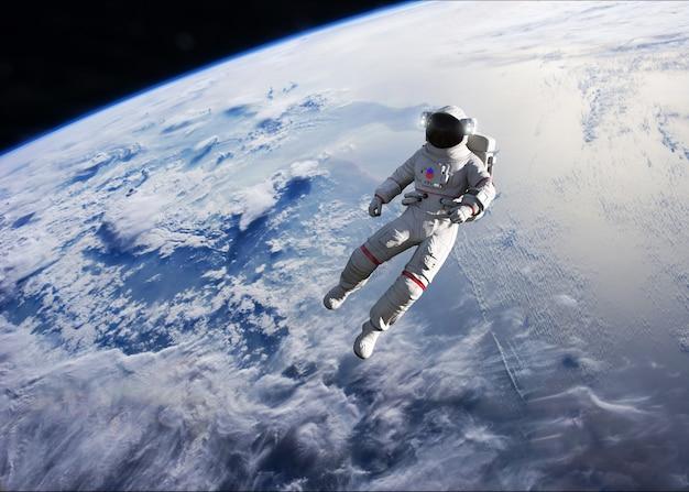 Astronaut conducting spacewalk on earth orbit. Premium Photo