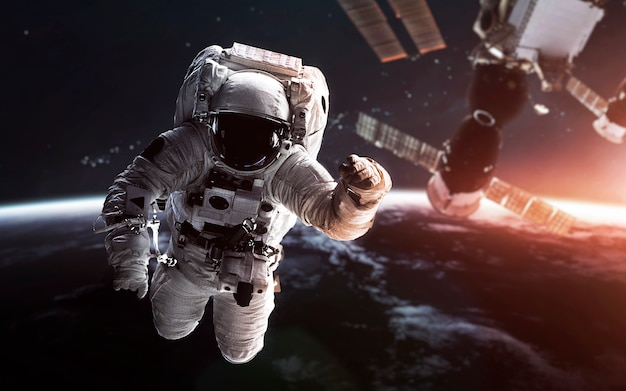 Astronaut at the earth orbit with the space station behind. Premium Photo