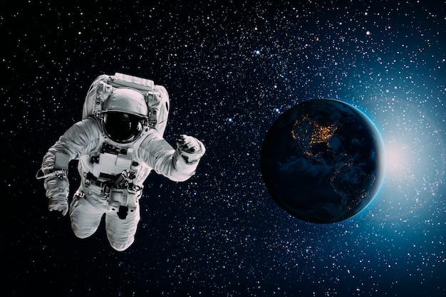 Астронавт летит над землей в космосе Premium Фотографии