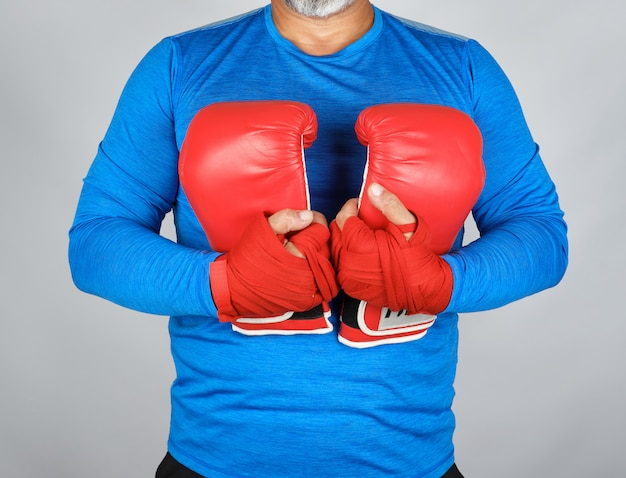 Athlete in blue clothes holding a pair of leather boxing gloves Premium Photo