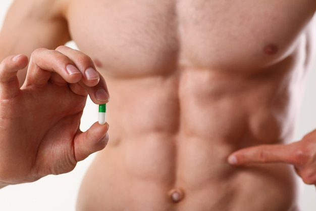 Athlete bodybuilder takes dope in the form of tablets form of pharma rapid progress in muscle development Premium Photo